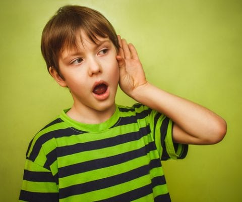 baby teenager boy listens to put a hand to his ear on a green background gray large-img-blog